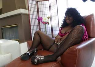 Curly haired ebony woman Layton Benton in fishnet stockings shows off her large natural tits during the time that engulfing a large black cock. Busty lady gets a mouthful of cum for your viewing joy